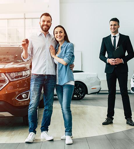Un vendeur de concession conclu la vente d'une voiture avec un couple