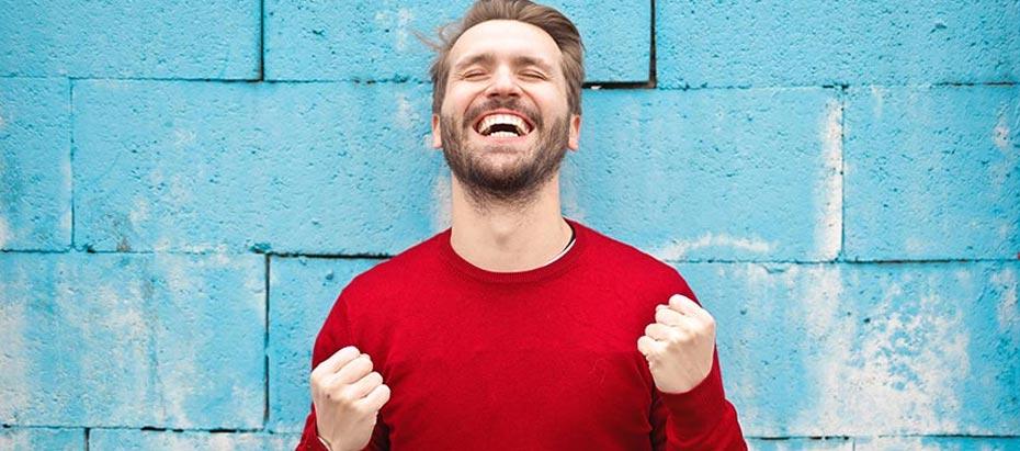 Un homme les poings levés heureux de sa réussite