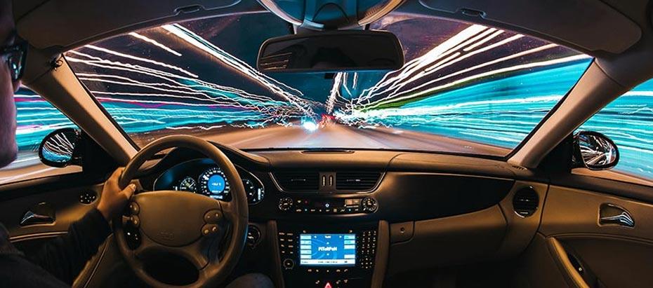 Un homme conduit un véhicule de nuit dans une ville