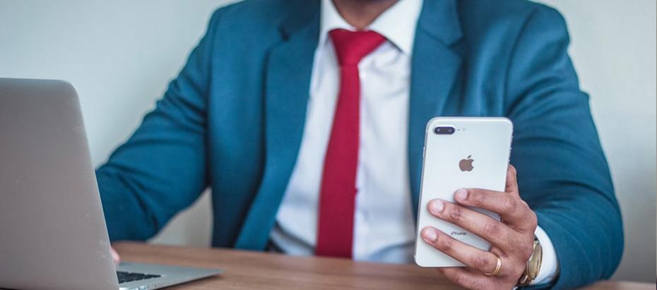 Un homme en costume avec son téléphone à la main