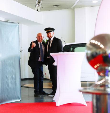 Photo du coach UpYourBizz et un vendeur content dans le showroom d'une concession