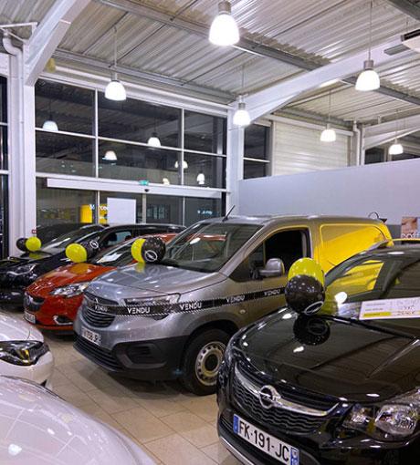 Un showroom remplit de véhicules en vente décorés pour les Olympiades