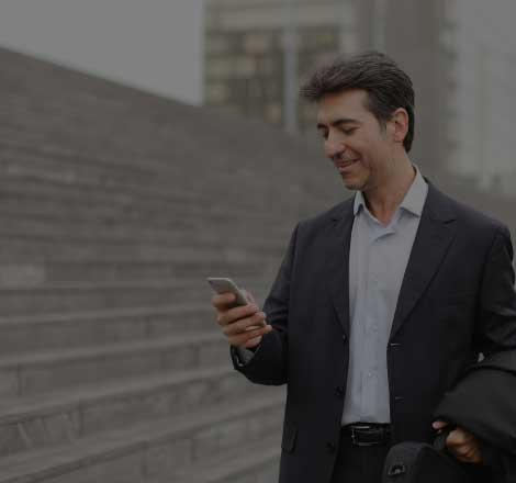 Un homme dans la rue regarde son téléphone