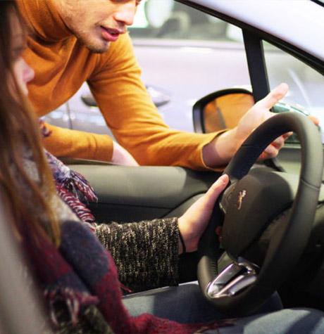 Une cliente assise au volant d'un véhicule et un vendeur lui montre ses fonctionnalités