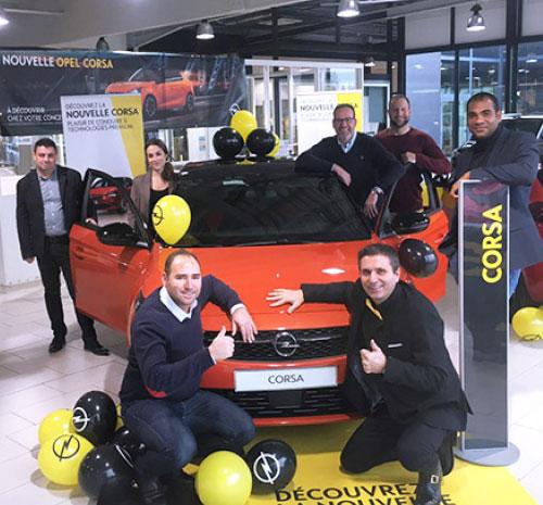 Les vendeurs et le coach pose devant une Opel Corsa décorée avec des ballons gonflables