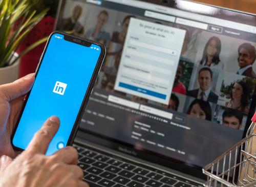 Une personne consulte LinkedIn sur son smartphone et pc