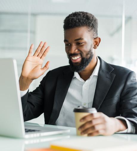 Un expert salut un client à travers son ordinateur grâce à Visio-Live