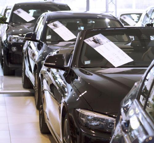 Véhicules stationnés en masse dans un showroom avec des affichettes de prix