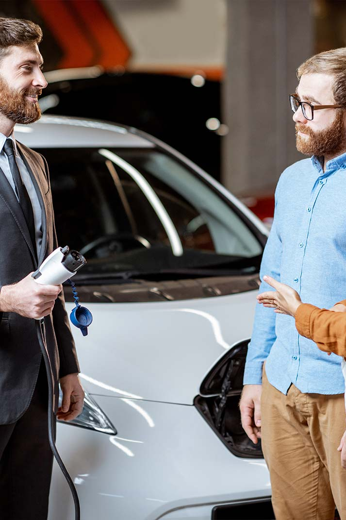 Des clients sont en discussion avec un vendeur de concession