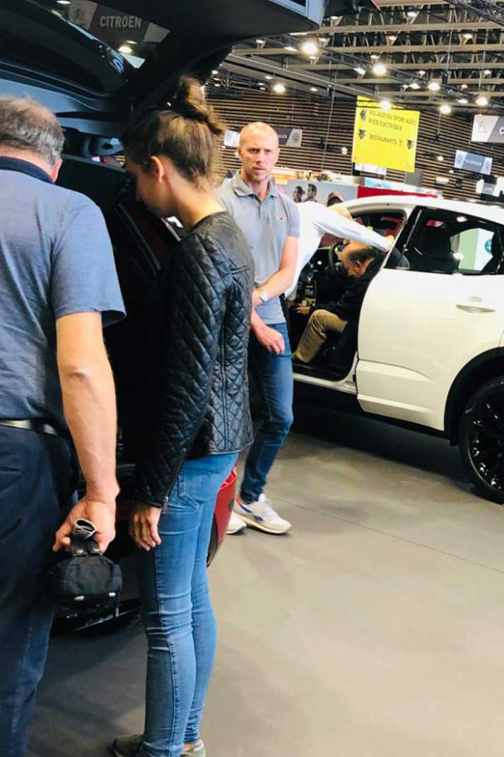 Ces personnes regardent des voitures dans une concession automobile