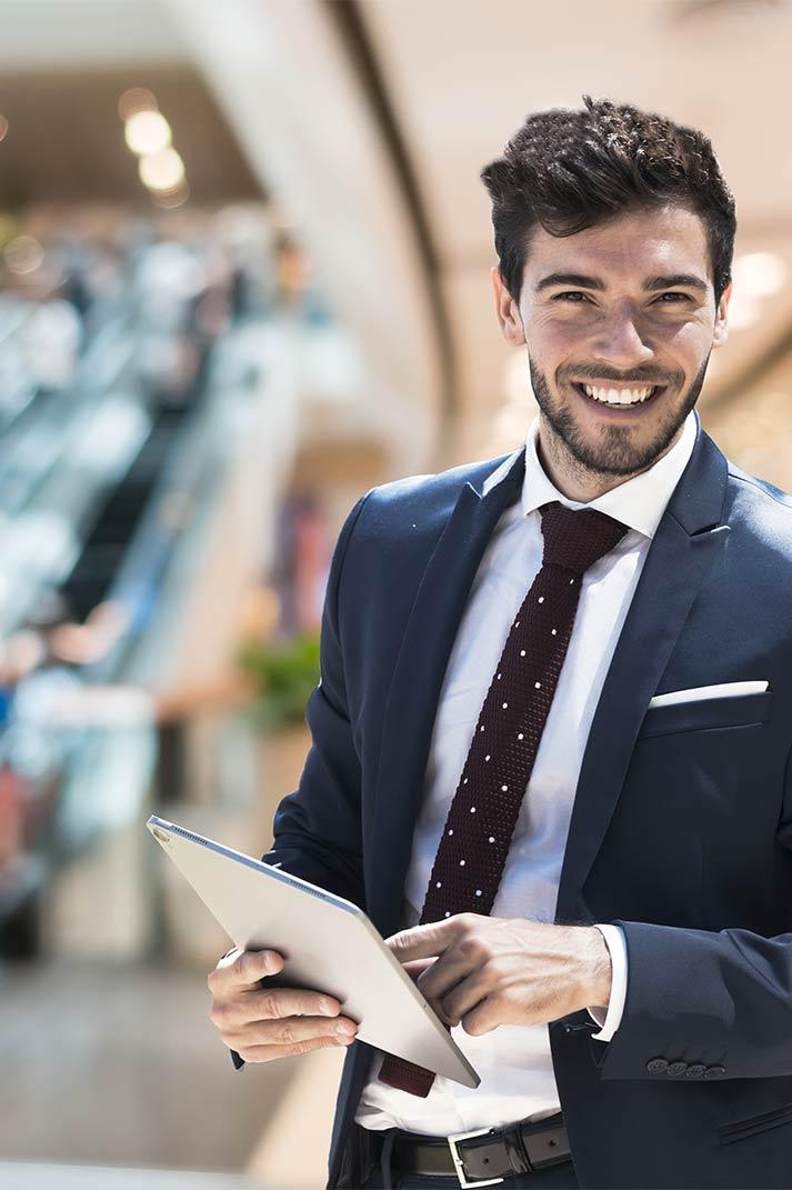 Animateur d'événement souriant et tablette à la main dans un centre commercial