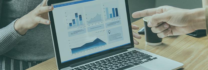 Une personne désigne des graphiques montrés par une femme sur un ordinateur