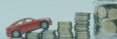 Une voiture miniature positionné sur des piles de pièces de monnaie