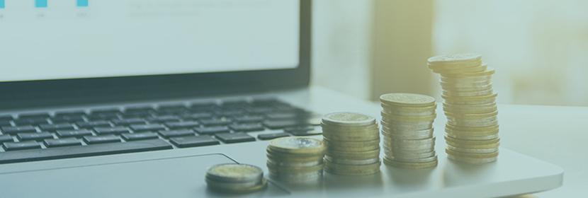 Succession de pile de pièces de monnaie sur un ordinateur portable