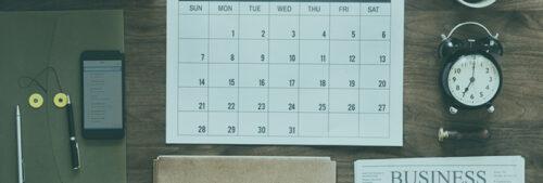Planning horloge téléphone portable stylos et journal sur un bureau