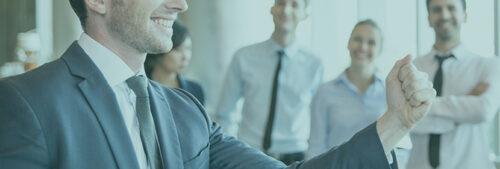 Un homme lève le poing et souris devant un groupe de personnes