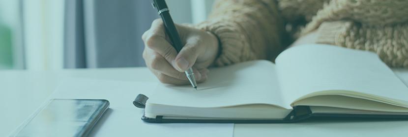 Une personne écrit sur un cahier
