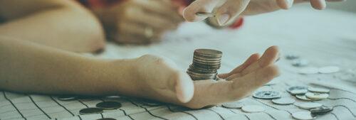 Une personne fait une pile de pièces de monnaie dans sa main