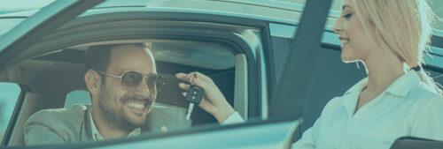 Une vendeuse tend des clés à un homme à l'intérieur d'une voiture