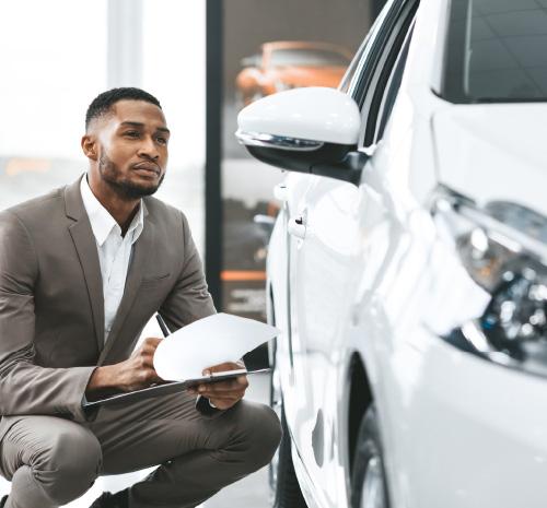 Un vendeur prends des notes sur un véhicule