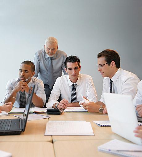 Un formateur accompagne des conseillers commerciaux assis autour d'une table