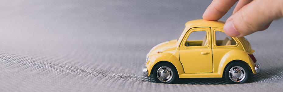Une personne fait rouler une voiture miniature jaune