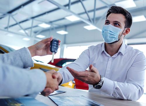 Un vendeur tend une clé de voiture à son client masqué et lui sert la main