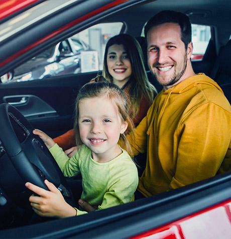 Une famille souriante dans une voiture rouge