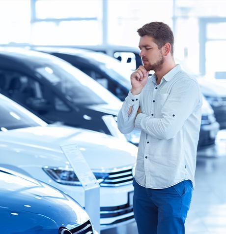 Un homme en concession réfléchi en regardant une voiture