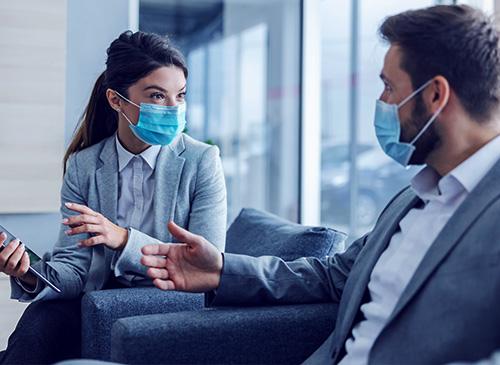 Une vendeuse et son client masqués discute en concession