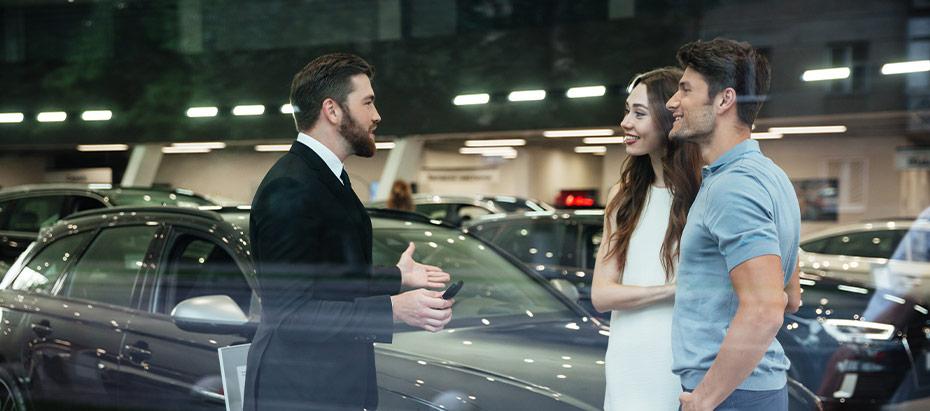 Un vendeur accueille un couple de client pendant la porte ouverte organisée par la concession